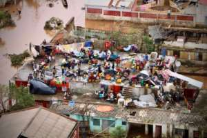 People gather on the roof of a house in Buzi. Some survivors say they have lost all their possessions. By ADRIEN BARBIER (AFP)