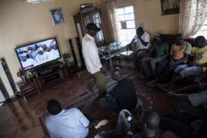 People gather in a house to watch the inauguration of Gambia's new president Adama Barrow on television inside a house in Serrekounda town, Banjul on January 19, 2017