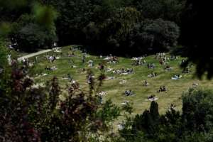 People enjoy the sun in Paris's Parc des Buttes Chaumont, as the French capital reopens it parks and gardens.  By ALAIN JOCARD (AFP)