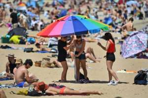 People enjoy the warm weather on Melbourne's St Kilda Beach after the Australian city began to lift virus restrictions.  By William WEST (AFP/File)