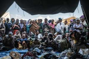 People fleeing violence in the Metekel zone gather outside a tent where clothes are being distributed at a camp in Chagni, Ethiopia.  By EDUARDO SOTERAS (AFP)