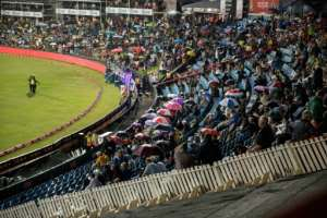People hold up umbrellas as as they wait for start of the first match between South Africa and Sri Lanka on January 20, 2017 at Supersport park, which ended in a 126-5 victory for South Africa.  By Gianluigi Guerica (AFP)