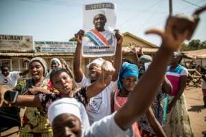 People hold a banner with an image of Gambia's opposition candidate Adama Barrow as they celebrate his victory in the Presidential Elections, in Serekunda, Banjul, on December 2, 2016