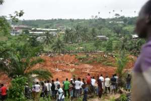 People look at the site of a landslide that killed at least 13 people in Anyama, a suburb of Abidjan..  By SIA KAMBOU (AFP)