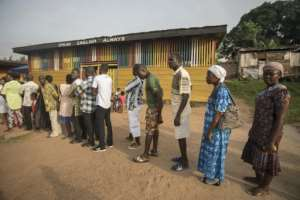 People line up to vote at a polling station in Kibi, southern Ghana, on December 7, 2016