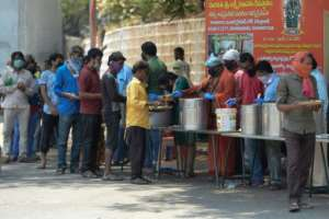 People line up in the Indian city of Hyderabad to receive free food distributed by a Hindu group during a government-imposed nationwide lockdown.  By NOAH SEELAM (AFP)