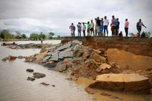 People stand beside a damaged section of the road between Beira and Chimoio in Nhamatanda district, central Mozambique. By ADRIEN BARBIER (AFP)