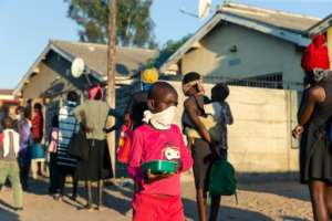 People queue in Chitungwiza for hot meals.  By Jekesai NJIKIZANA (AFP/File)