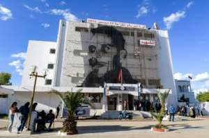 People queue up outside the main post office on Mohamed Bouazizi Square, its facade displaying a picture of Bouazizi, who set himself on fire ten years ago.  By Fethi Belaid (AFP)