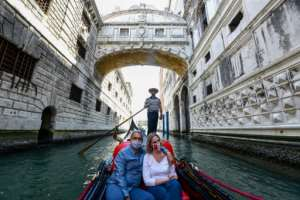 People ride in a gondola in Venice as Italy eases its virus lockdown.  By ANDREA PATTARO (AFP)