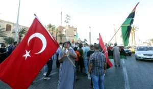 People wave flags of Libya (R) and Turkey (L) during a demonstration in Tripoli.  By Mahmud TURKIA (AFP)