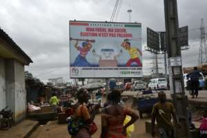 People walk past a billboard in Abidjan urging peaceful elections next month.  By SIA KAMBOU (AFP)