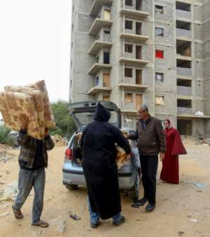 People unload donated furniture for displaced families.  By Mahmud TURKIA (AFP)