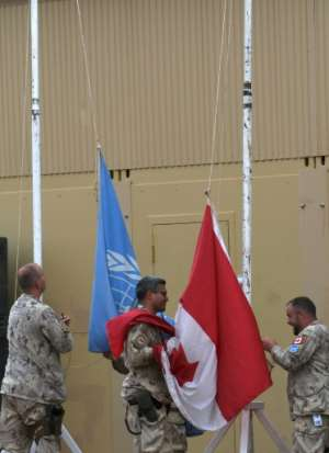 Peacekeepers raise the Canadian flag alongside the UN flag at the camp in Gao.  By SEYLLOU (AFP)