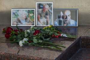Photographs of Russian journalists (L-R) Alexander Rastorguyev, Kirill Radchenko and Orkhan Dzhemal, who were killed in Central African Republic, were left outside the Central House of Journalists in Moscow.  By Vasily MAXIMOV (AFP)