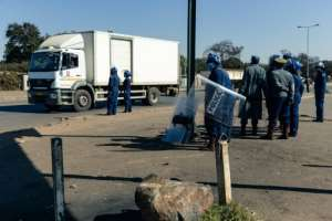 Police ask for travel documents at a road block in Mbare, a township in the suburbs of Harare.  By Jekesai NJIKIZANA (AFP)