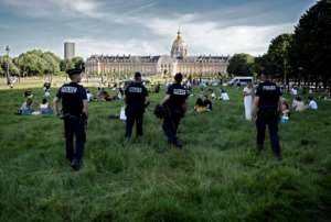 Police ask to people to follow physical distancing rules in front of the hotel des Invalides in Paris.  By THOMAS COEX (AFP)