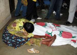 A relative mourns over the body of a victim of armed raiders in Bujumbura.  By Esdras Ndikumana (AFP/File)
