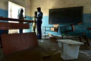 Police officers at the Hankounou polling station where ballot materials were vandalised.  By TONY KARUMBA (AFP)