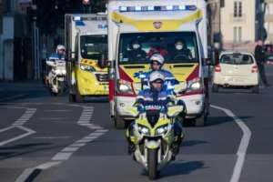 Police officers escort an ambulance carrying patients infected with the covid-19 disease in Nantes, France.  By Loic VENANCE (AFP)