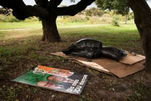 Politics and poverty: A campaign poster lies alongside the bedding of a homeless person in a Cape Town park ahead of the country's elections in May.  By RODGER BOSCH (AFP)