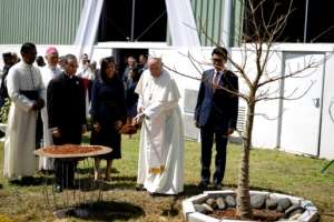 Pope Francis planted a baobab tree with Madagascar President Andry Rajoelina at the presidential palace in Antananarivo.  By MARCO LONGARI (AFP)