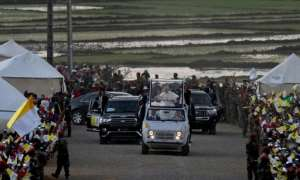 Pope Francis waved to the crowds as he arrived for a vigil with young people in Antananarivo.  By Tiziana FABI (AFP)