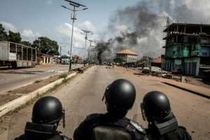 Plumes of black smoke rose over an opposition stronghold in the capital Conakry, where protesters erected barricades and lit fires.  By JOHN WESSELS (AFP)