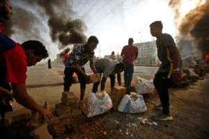 Protesters build a brick barricade on Street 60, one of the main streets in the capital.  By ASHRAF SHAZLY (AFP)