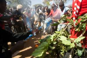 Protesters burns shirts and flags from the recently re-elected Malawian president Arthur Mutharika's Democratic Progressive Party as part of the demonstrations in Lilongwe.  By AMOS GUMULIRA (AFP)