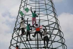 Protesters climb a telecommunication mast while carrying the Nigerian national flag.  By Kola Sulaimon (AFP)