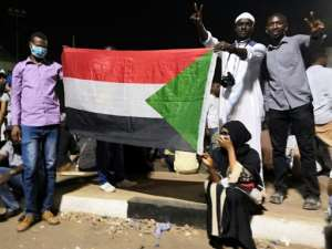 Protesters hold the national flag, after Sudan's police on Tuesday ordered officers to avoid intervening against protesters. By - (AFP)