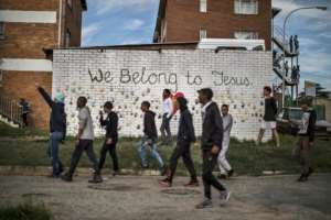 Protesters pass in front of a mural in Johannesburg as they faced off against police. By MARCO LONGARI (AFP)