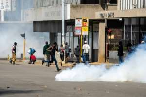 Protesters rushed for cover as police fired tear gas.  By Zinyange Auntony (AFP)