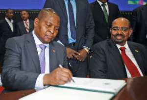 President Faustin Archange Touadera initials the peace agreement his government reached in Khartoum with 14 armed groups.  By ASHRAF SHAZLY (AFP)