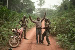 Rangers search a motorcycle taxi for pangolin scales or ammunition.  By FLORENT VERGNES (AFP)
