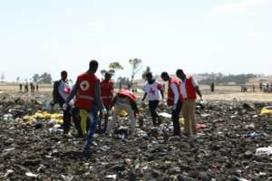 Red cross teams work through the debris after an Ethiopia Airlines flight to Nairobi crashed shortly after take-off from Addis Ababa, killing all 157 on board.  By Michael TEWELDE (AFP)
