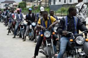 Regular motorcycle taxis queue for custom in Lagos -- helmets and safety kits are absent, and passengers have to haggle over fares.  By PIUS UTOMI EKPEI (AFP)