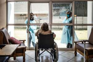 Relatives in protective gear chat to a resident through a window to reduce the risk of virus infection.  By MARCO LONGARI (AFP)