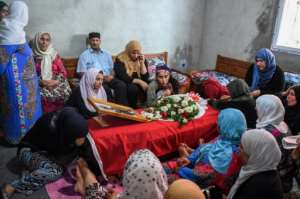Relatives of Tunisian police officer Arbi Guizeni, killed in a jihadist attack Sunday, mourn over his coffin at their home in capital Tunis on July 9, 2018.  By FETHI BELAID (AFP)