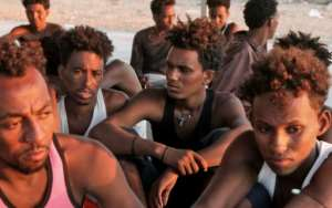 Rescued migrants sit on the coast of Khoms, some 100 kilometres (60 miles) from the Libyan capital Tripoli, on July 26, 2019.  By - (AFP)