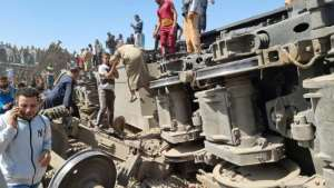 Rescuers gather around the overturned wreckage of two passenger trains that collided in the Tahta district of southern Egypt, killing at least 32 people.  By - (AFP)