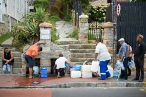 Residents from the Cape Town area collect drinking water from pipes, as a three-year-long drought grips the city.  By RODGER BOSCH (AFP/File)