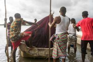 Residents of Alongo village use a boat to transport the Zangbeto, a traditional voodoo guardian, not, as once, to maintain law and order, but to help protect the rich mangrove ecosystem.  By YANICK FOLLY (AFP)