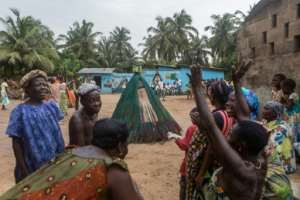 Residents of the village in a region battling the effects of over-fishing and shrinking forests dance near the Zangbeto.  By YANICK FOLLY (AFP)