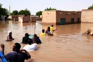 Residents wade through flood waters in Wad Ramli village on the eastern banks of the Nile river.  By Ebrahim HAMID (AFP)