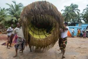 Residents transport a Zangbeto ahead of a traditional Yoruba ceremony.  By YANICK FOLLY (AFP)