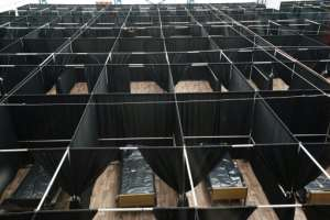 Rows of beds separated by black fabric are set up as a temporary field hospital for COVID-19 patients at the USTA Billie Jean King tennis center in New York.  By Bryan R. Smith (AFP)