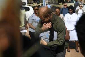 Royal embrace: The prince gives a youngster a hug at a charity for vulnerable children in Sentebale.  By MONIRUL BHUIYAN (AFP)