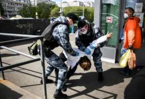 Russian National Guard (Rosgvardia) officers detain a man in front of a supermarket in Moscow after city authorities made it mandatory to wear gloves and a mask in pubic places.  By Alexander NEMENOV (AFP)